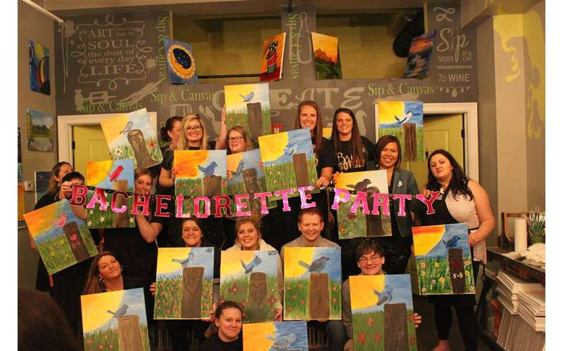 a group of paint and sip participants with their paintings and a bachelorette sign