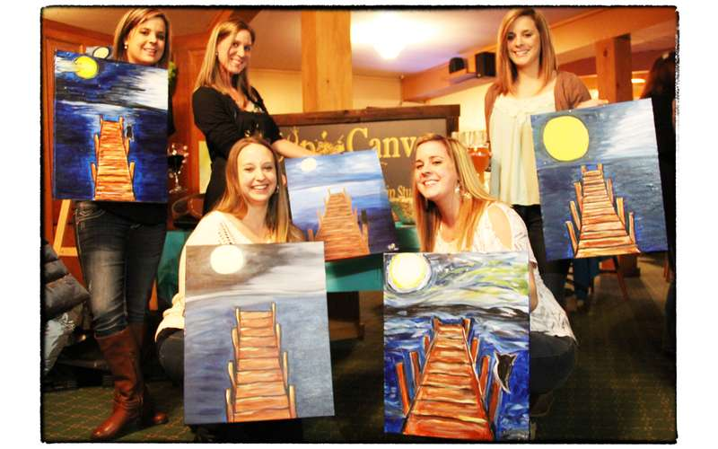 group of women holding up finished paintings