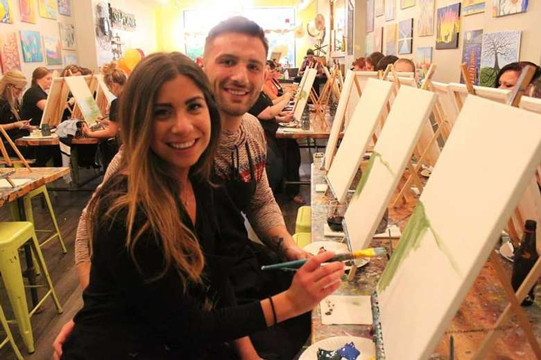 a man and woman painting at easels