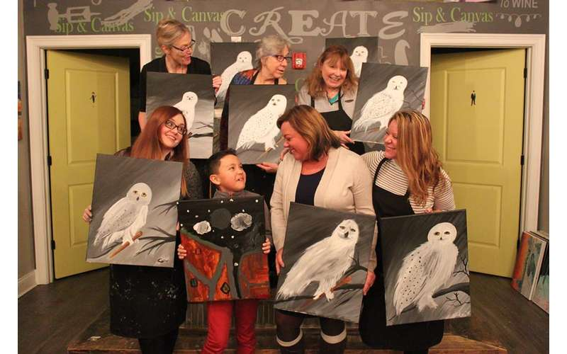 people holding paintings of white owls