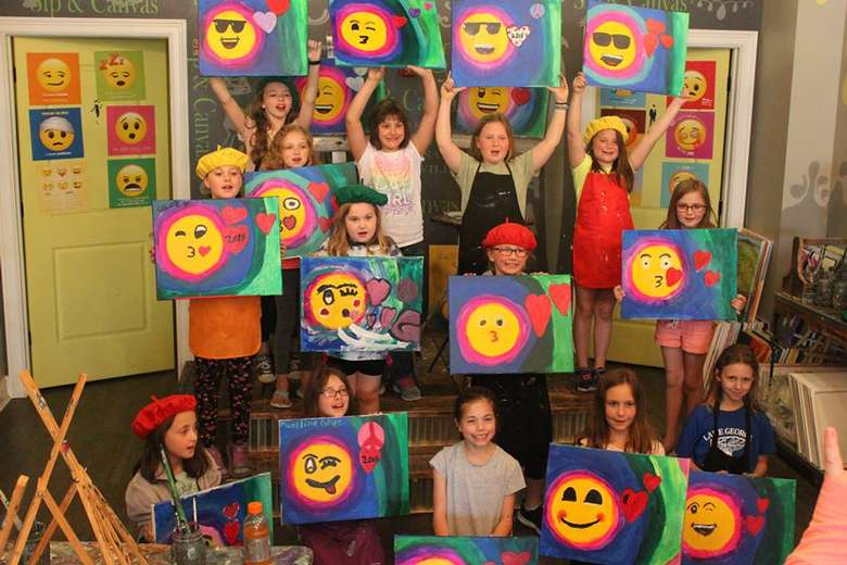 kids holding up colorful paintings