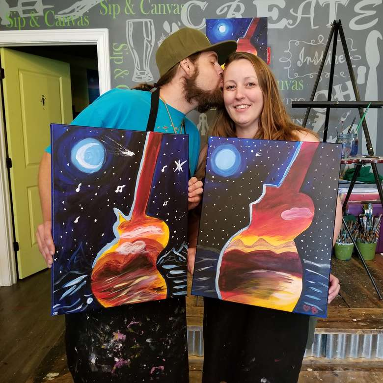 A couple holding their finished paintings of landscape in the silloutte of a guitar.