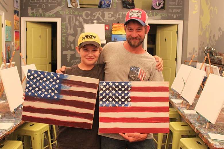 Father and son holding paintings of the American flag.
