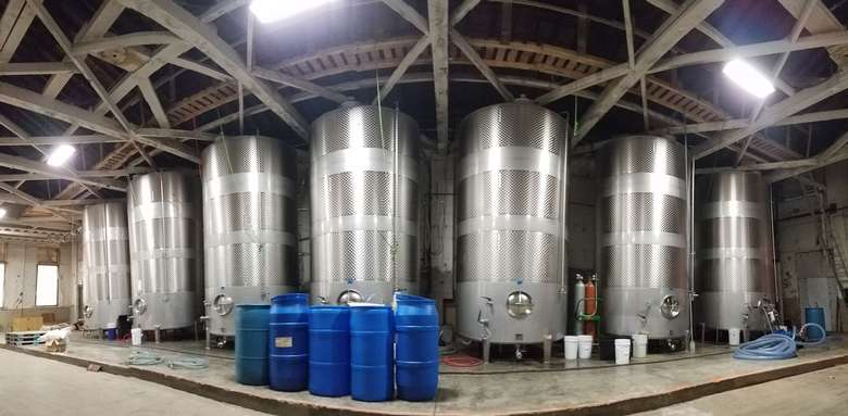 seven large metal tanks in a cidery's production warehouse