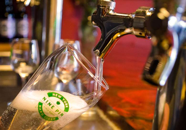 glass of nine pin draft cider being poured