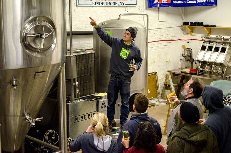 cider maker pointing to a large metal tank while talking to a tour group