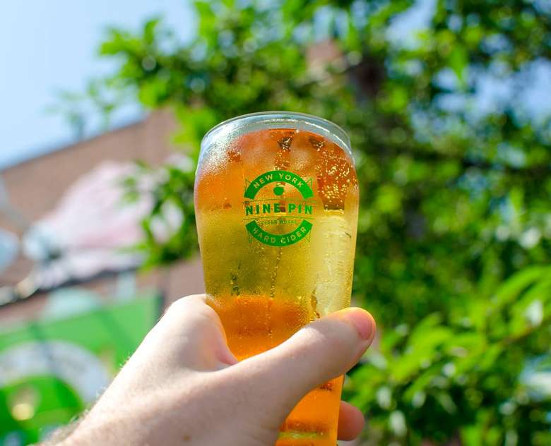 A glass of Nine Pin cider being raised in front of cidery building