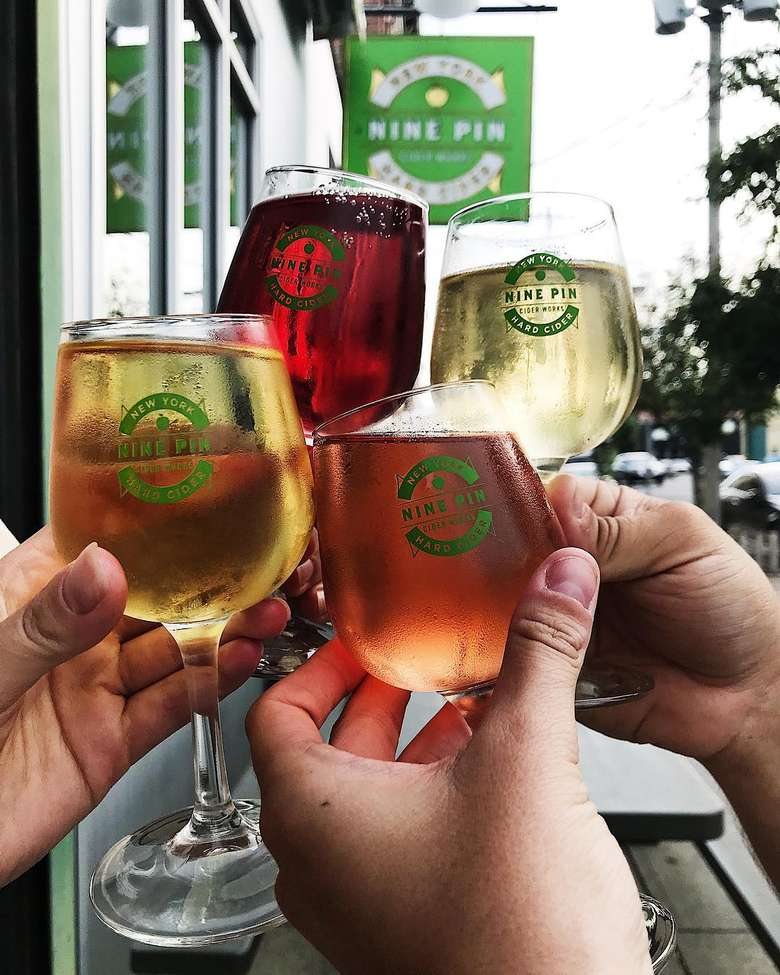 Four different Nine Pin ciders in small glasses in front of the Nine Pin cider sign
