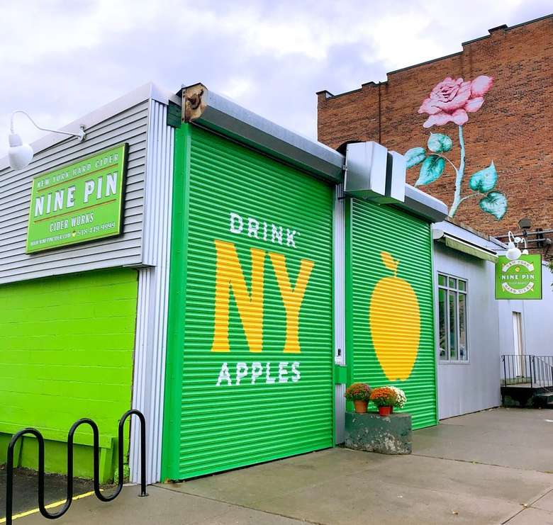 """Nine Pin Cider's front garage doors that read """"Drink NY Apples"""" with an image of an apple on second door"""