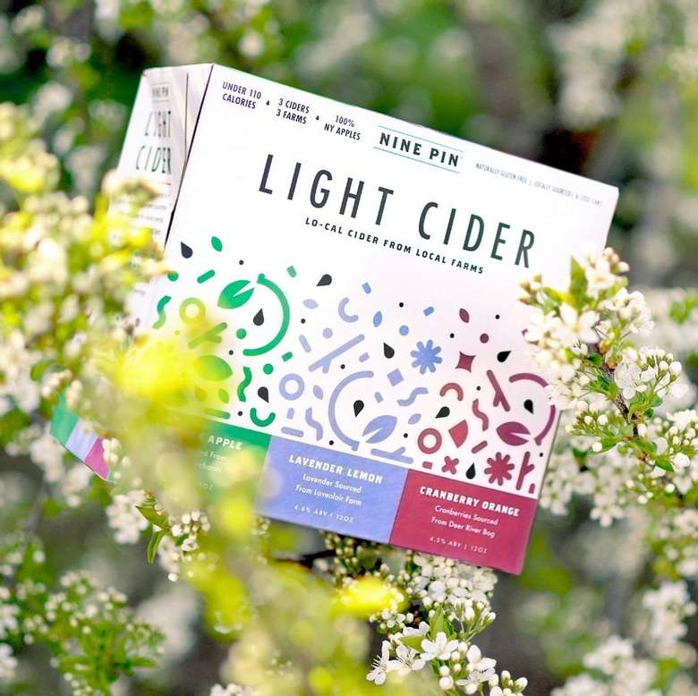 Box of Light Cider placed in a beautiful blooming bush