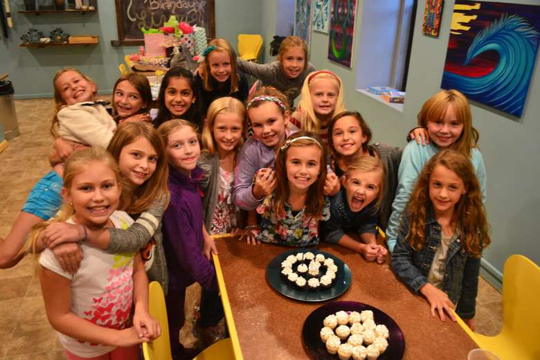 group of girls posing in front of two trays of cupcakes