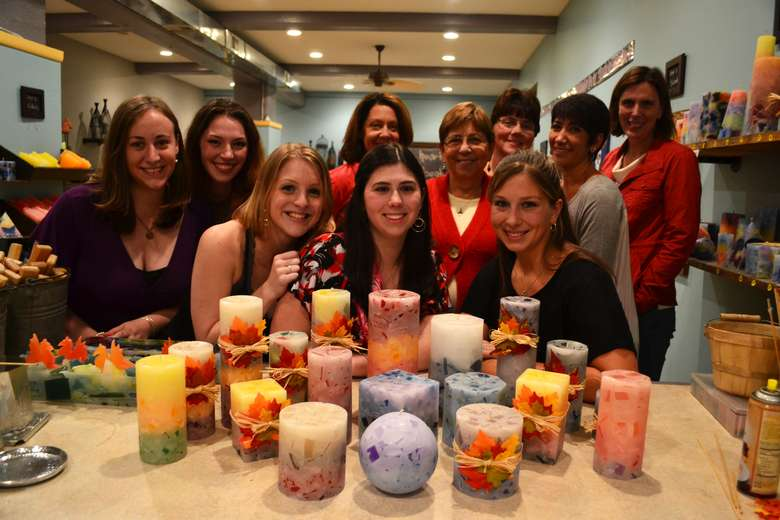 group of women posing behind a table of homemade candles