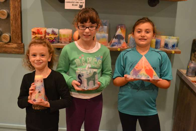 three young girls holding candles that they made