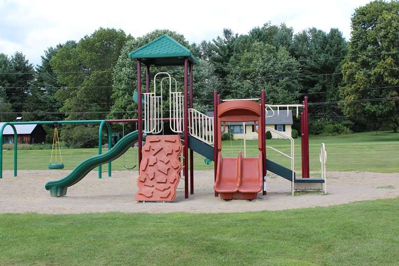a playground at a park with slides and a climbing section