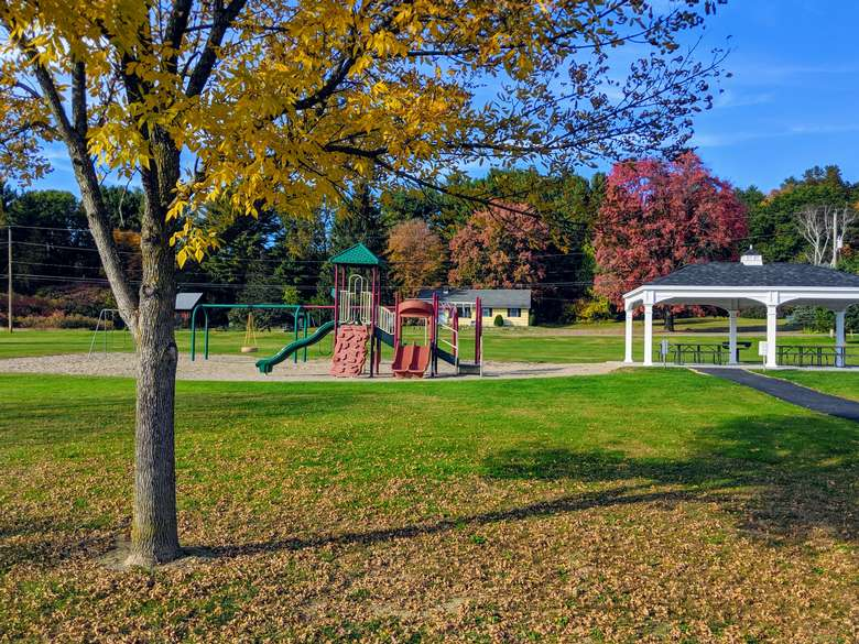 playground and picnic tables under gazebo structure in fall