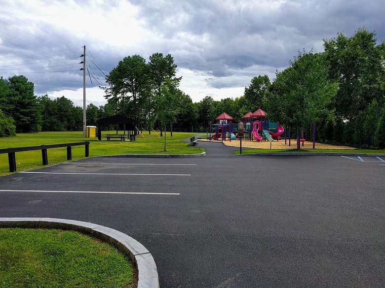 a parking lot at a park near a playground