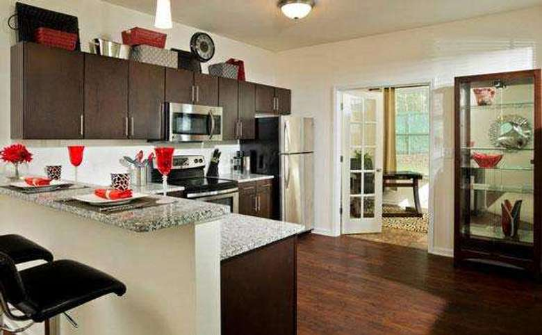 kitchen with dark cabinets, granite countertops, and bar-style seating