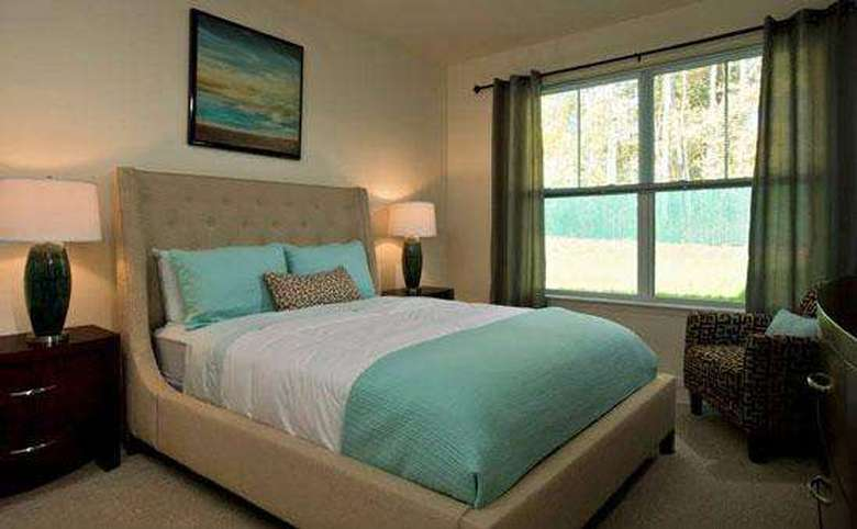 a bedroom with white and teal bedding