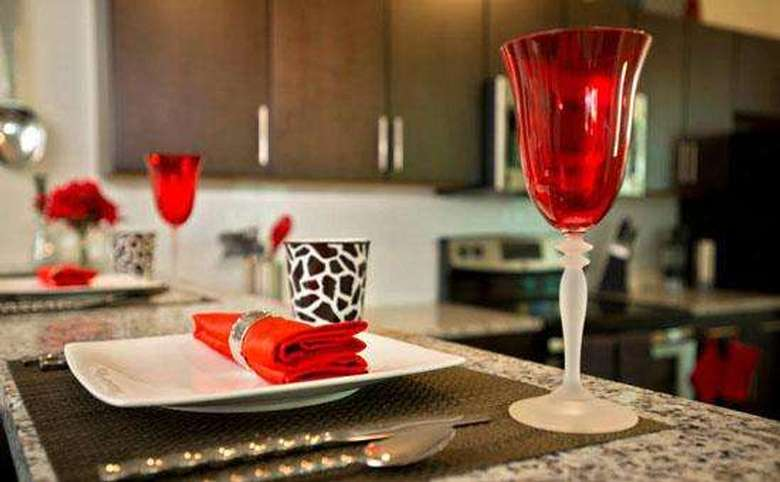 a place setting featuring a red chalice and a red napkin on a plate