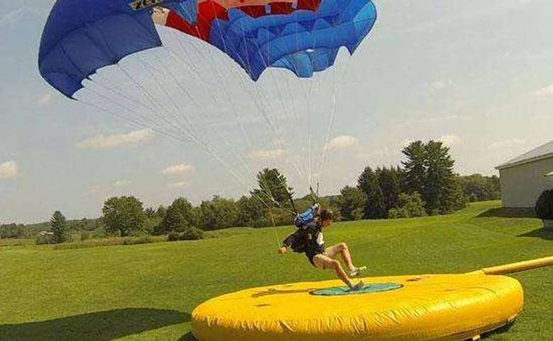 A skydiver landing perfectly on a yellow inflated pad