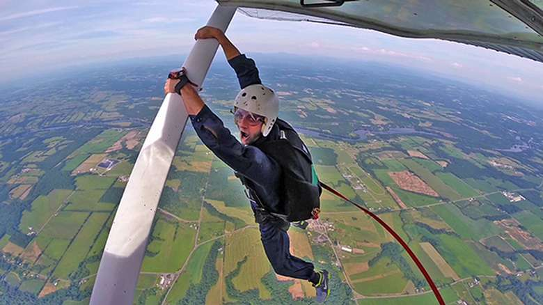 A skydiver hanging onto the side of a plane before jumping