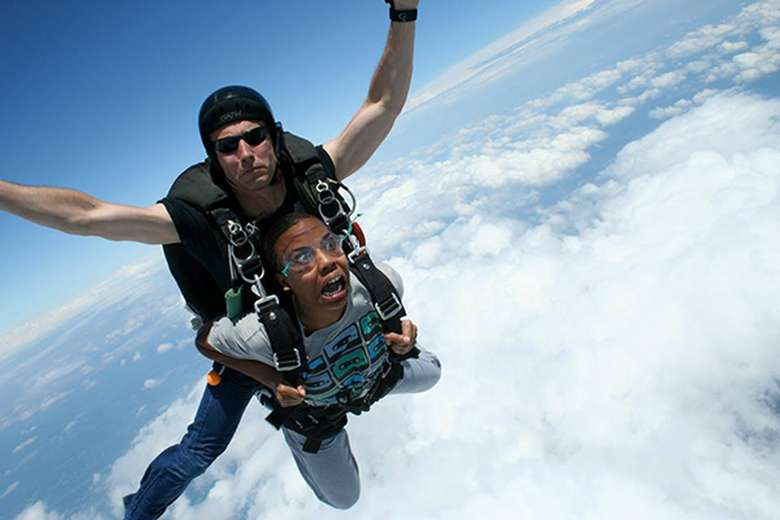 Person with a terrified face doing a tandem jump with a guide
