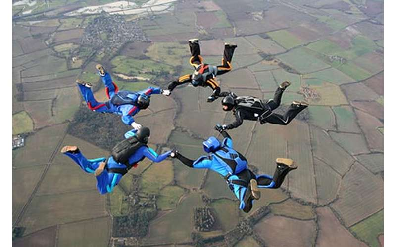 Five skydivers holding hands in a circle