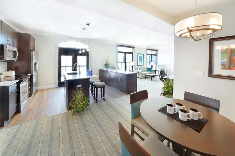 large bright kitchen in a hotel suite with a table and four chairs