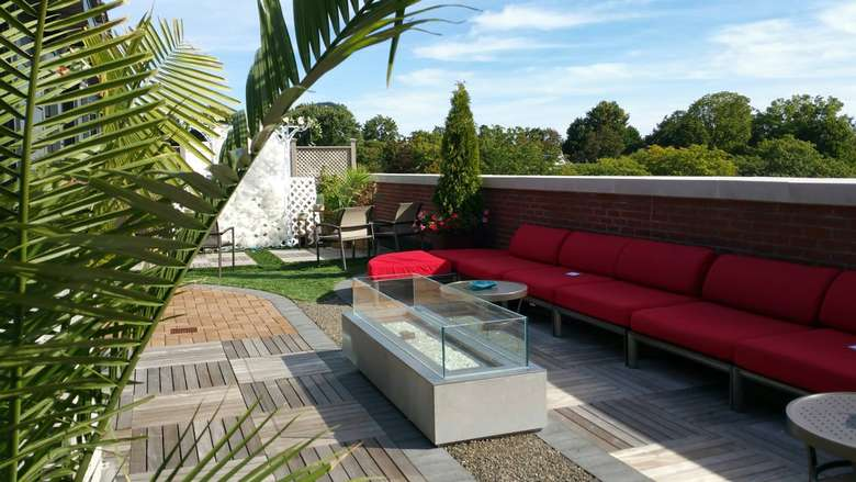 red couches on a rooftop deck with green ferns in the foreground