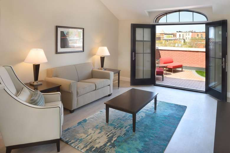 seating area in a hotel suite with french doors leading out onto a patio