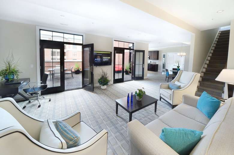 large seating area in a hotel suite with a kitchen in the background and french doors leading onto a patio