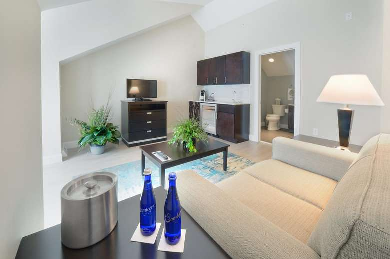 two blue bottles of saratoga water on a side table in a family room with a couch and a flat screen television