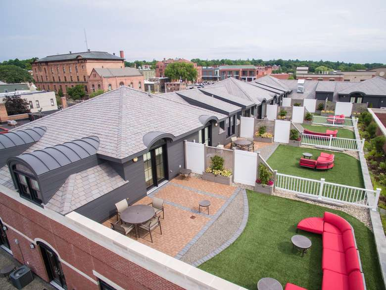 aerial view of rooftop decks at the pavilion grand hotel with red couches, green grass, and patio seating areas