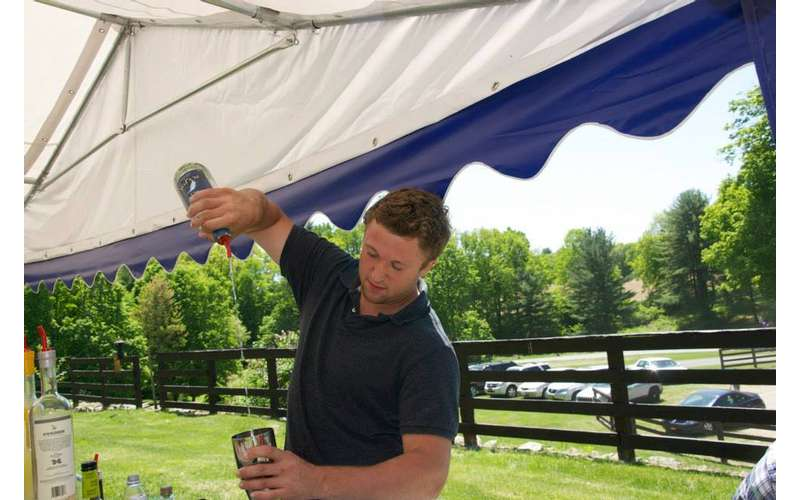 a man outdoors under a tent pouring a drink from a bottle