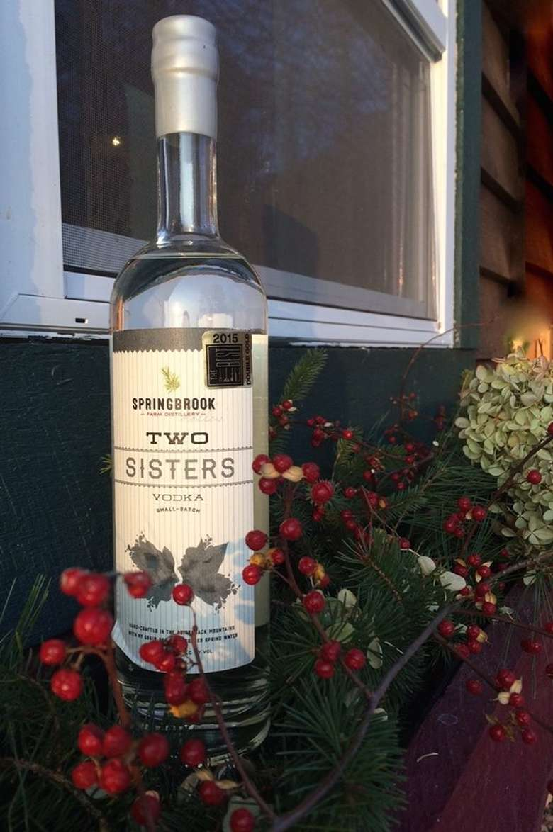 a bottle of two sisters vodka among flowers