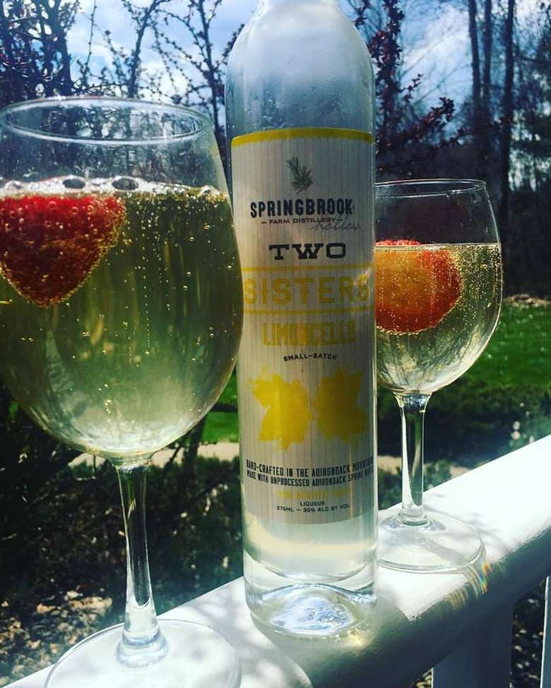 a bottle of limoncello between two full tasting glasses