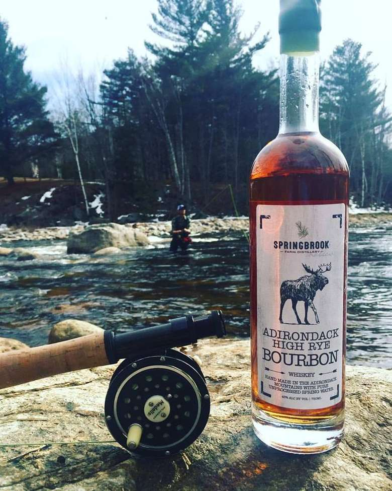 a bottle of adirondack high rye bourbon on a rock in front of a river