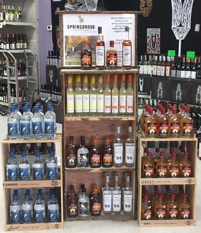 many bottles of spirits from springbrook hollow on shelves in a store