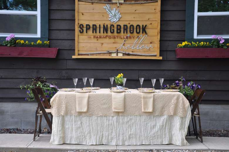 a row of glasses on a table in front of springbrook hollow farm distillery
