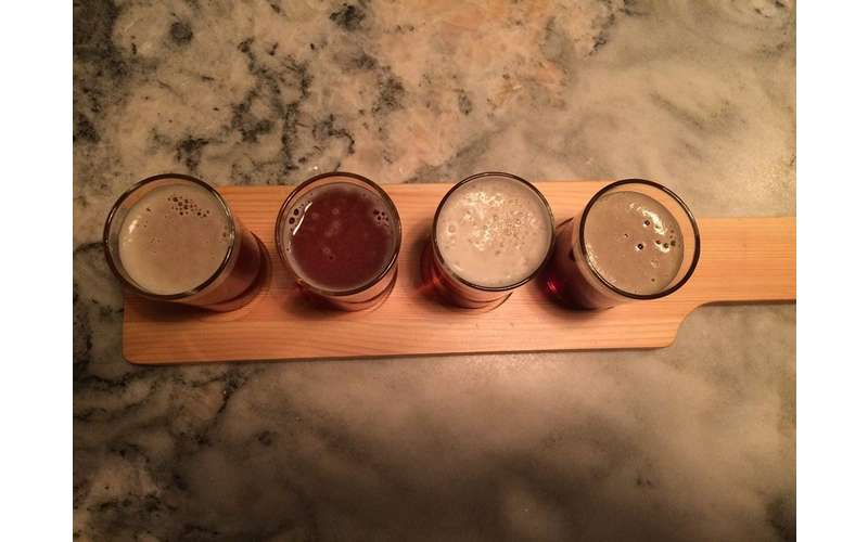 four full tasting glasses in a tow on a small wooden board