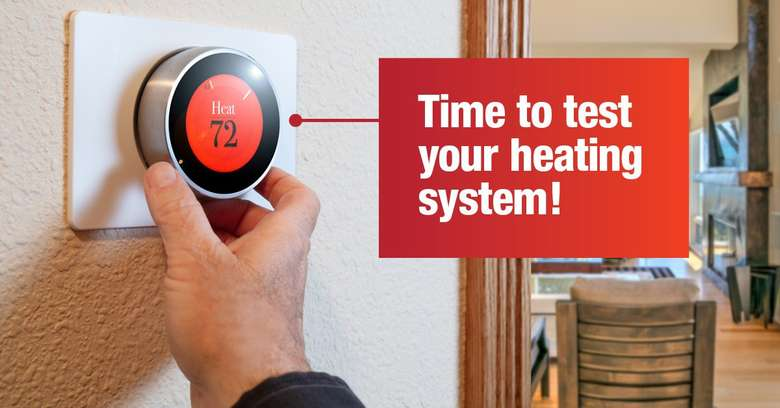person holding onto heating control system, and the words time to test your heating system are on the photo