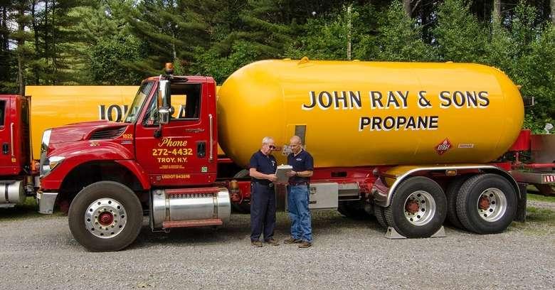 two men standing near propane truck