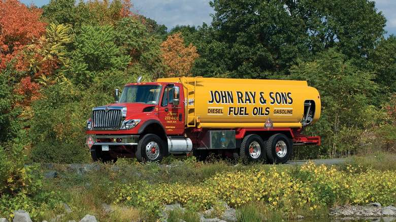 a red and yellow truck with the words john ray and sons fuel oils