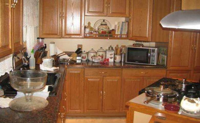 cluttered kitchen with lots of stuff on the counters