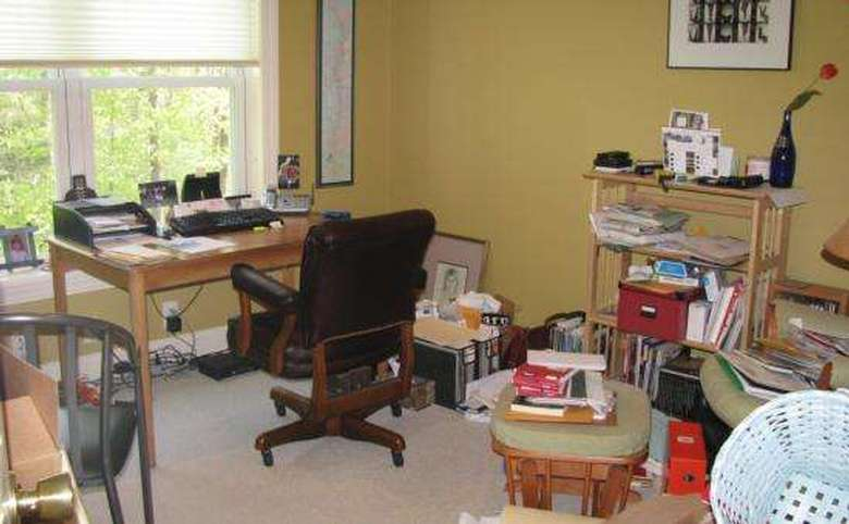 cluttered home office with lots of stuff on the floor