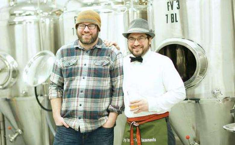 two men standing in front of brewing equipment