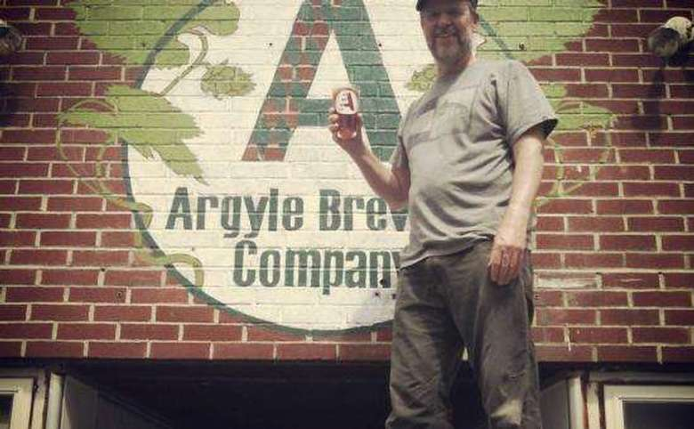 man standing in front of and pointing at an argyle brewing company logo painted on a brick building