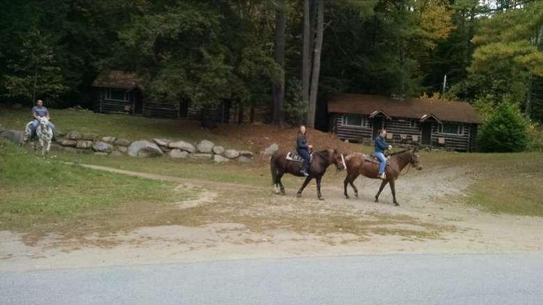 three people riding horses near cabins