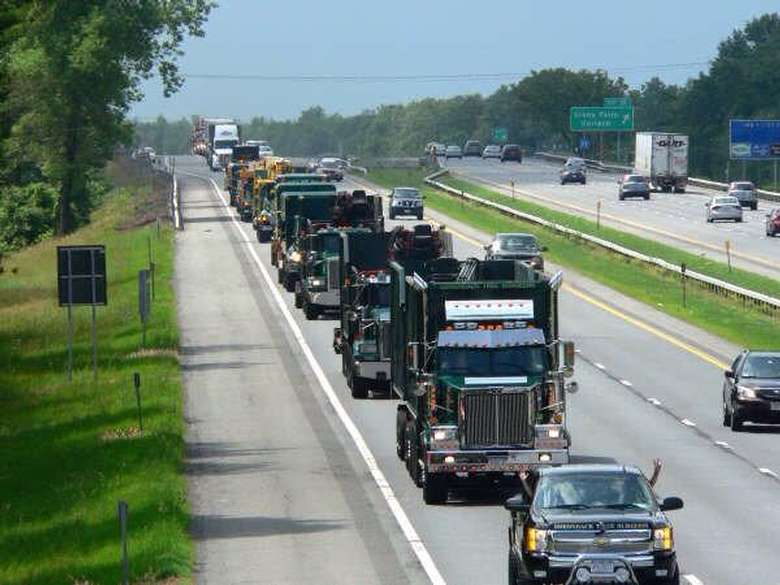fleet of tree removal vehicles driving down the highway