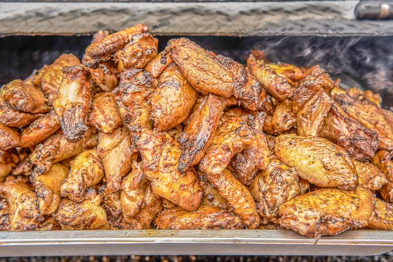 very large pile of smoked chicken wings stacked in smoker